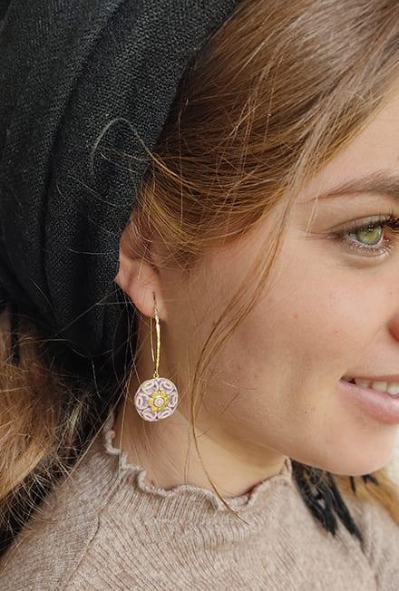 עגילים יחודיים עבודת יד מסותתים מחימר עם שכבת גלזורה ועיטורי זהב 14 קארט על גבי מתלה העשוי גולדפילד.