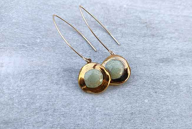 עגילים יחודיים עבודת יד מסותתים מחימר עם שכבת גלזורה ועיטורי זהב 24 קארט על גבי מתלה העשוי גולדפילד.