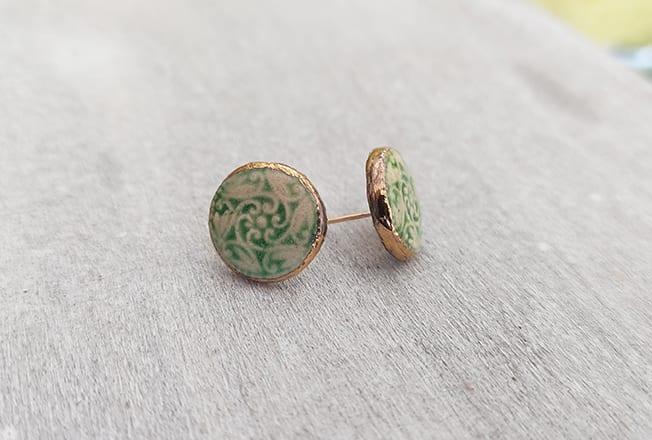 עגילים יחודיים עבודת יד מסותתים מחימר עם שכבת גלזורה ועיטורי זהב 24 קארט על גבי תושבת העשויה גולדפילד.